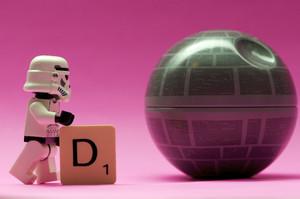 Ludzik Lego trzyma rękę na literze D i patrzy na kulę